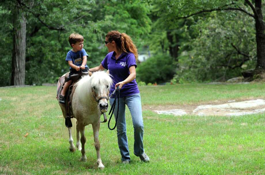 Danny Egan, 4, of Eastchester N.Y., rides a Pied Piper Pony with Jessica Pavella of Patterson N.Y., at Bruce Museum Family Day- Egg Fair at Bruce Museum in Greenwich, Conn., Sunday, July 21, 2013. Photo: Helen Neafsey / Greenwich Time