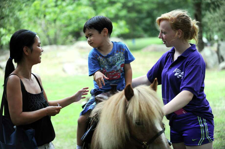 Samantha Eagan, of Eastchester, N.Y., speaks to his son, Danny, 4, before he rides with Jessica Pavella, of Patterson, N.Y., from Bruce Museum Family Day-Eggs Day at Bruce Museum in Greenwich, Conn., Sunday, July 21, 2013. Photo: Helen Neafsey / Greenwich Time