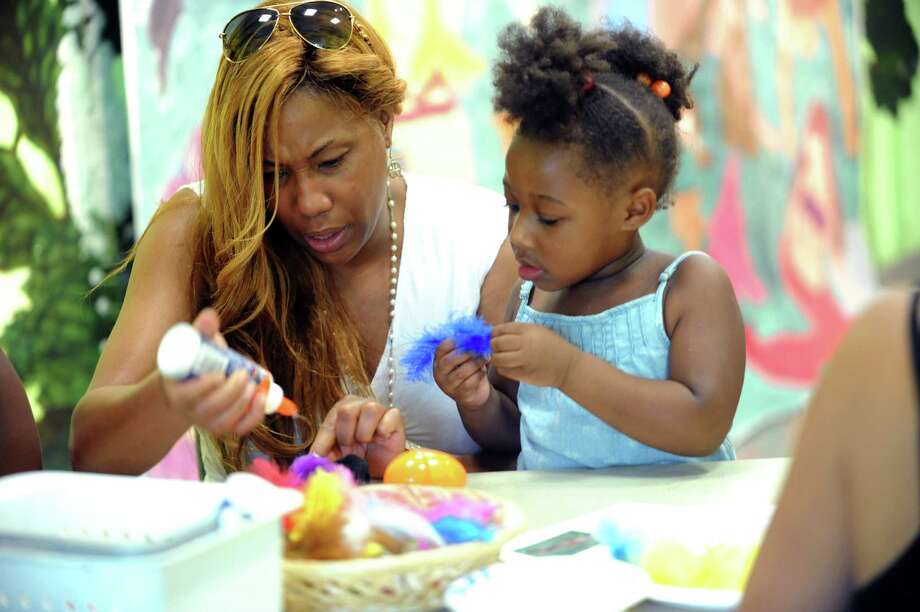 Evette Murtha, of Stamford, helps her granddaughter Dior Barnes, 3, make a eggs at Bruce Museum Family Day, Fair Day at Bruce Museum in Greenwich, Conn., Sunday, July 21, 2013. Photo: Helen Neafsey / Greenwich Time