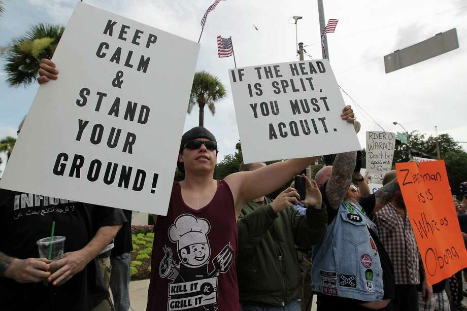Protestors hold signs up as the G. Zimmerman River Oaks Stand Your Ground group holds a counter demonstration to Houston community activist Quanell X lead group march a march in the River Oaks community to protest a Florida jury's acquittal of George Zimmerman in the shooting death of Trayvon Martin. Sunday, July 21, 2013, in Houston. Photo: James Nielsen, Houston Chronicle / © 2013  Houston Chronicle