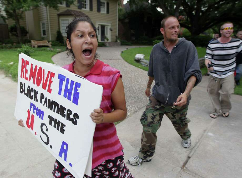 A protestors holds sign as the G. Zimmerman River Oaks Stand Your Ground group holds a counter demonstration to Houston community activist Quanell X lead group march a march in the River Oaks community to protest a Florida jury's acquittal of George Zimmerman in the shooting death of Trayvon Martin. Sunday, July 21, 2013, in Houston. Photo: James Nielsen, Houston Chronicle / © 2013  Houston Chronicle
