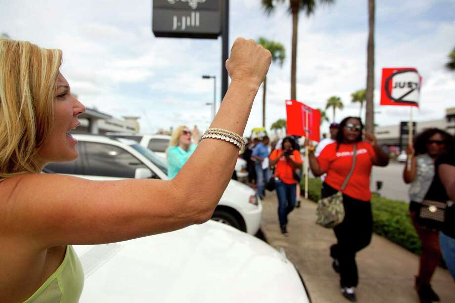 Crista Clark shows her support as nearly 1,000 people protested in the River Oaks community protested against a Florida jury's acquittal of George Zimmerman in the shooting death of Trayvon Martin Sunday, July 21, 2013, in Houston. Photo: Johnny Hanson, Houston Chronicle / © 2013  Houston Chronicle