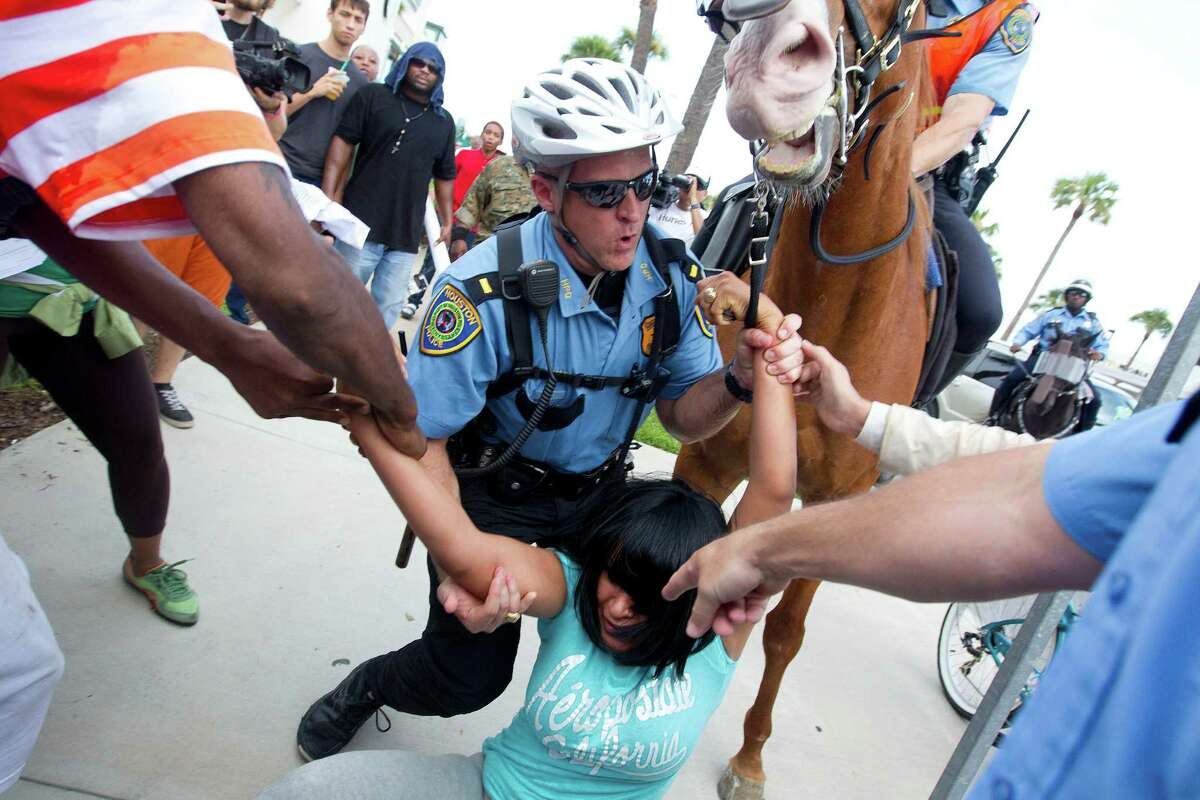A police officer attempts to help a woman who got her hand caught in the harness of a horse as nearly 1,000 people protested against a Florida jury's acquittal of George Zimmerman in the shooting death of Trayvon Martin in the River Oaks community on the corner of W. Gray and Shepherd Streets Sunday, July 21, 2013, in Houston.