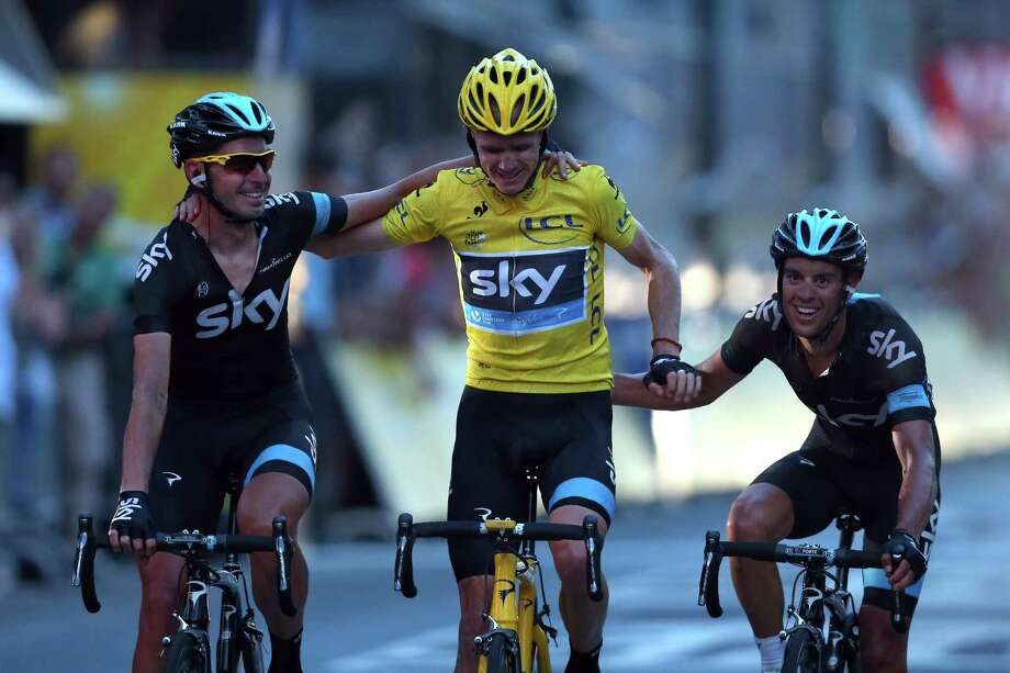 PARIS, FRANCE - JULY 21: Chris Froome of Great Britain and SKY Procycling (C) celebrates as he crosses the finish line flanked by teammates David Lopez (L) and Richie Porte during the twenty first and final stage of the 2013 Tour de France, a processional 133.5KM road stage ending in an evening race around the Champs-Elysees, on July 21, 2013 in Paris, France.  (Photo by Bryn Lennon/Getty Images) ORG XMIT: 169057550 Photo: Bryn Lennon / 2013 Getty Images