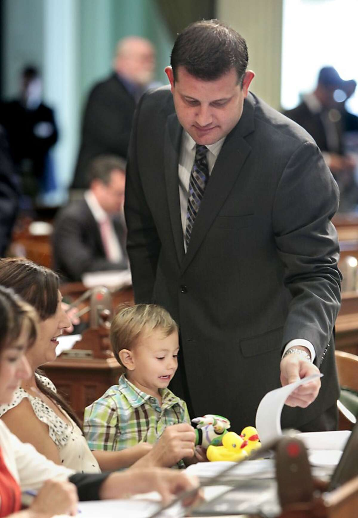 Lucas Valadao, 2, grimaces as he looks over the paper work his father, Assemblyman David Valadao, R-Hanford, was reviewing, at the Capitol in Sacramento, Calif., Thursday, June 28, 2012. Valadao's children and wife Terra, second from left, accompanied the lawmaker during Thursday's Assembly session. At left is Assemblywoman Diane Harkey, R-Dana Point.(AP Photo/Rich Pedroncelli)