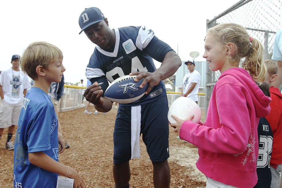 Young fans Skyler Ohlmeyer (right) and Brandon Gorski get an autograph from Dallas Cowboys defensive end DeMarcus Ware (94) at the Cowboys training camp on Sunday, July 21, 2013 in Oxnard. Photo: Kin Man Hui, San Antonio Express-News / ©2013 San Antonio Express-News