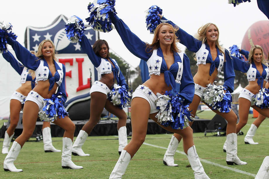 The Dallas Cowboys cheerleaders perform during the kick off of the 2013 Dallas Cowboys training camp on Sunday, July 21, 2013 in Oxnard. Photo: Kin Man Hui, San Antonio Express-News / ©2013 San Antonio Express-News