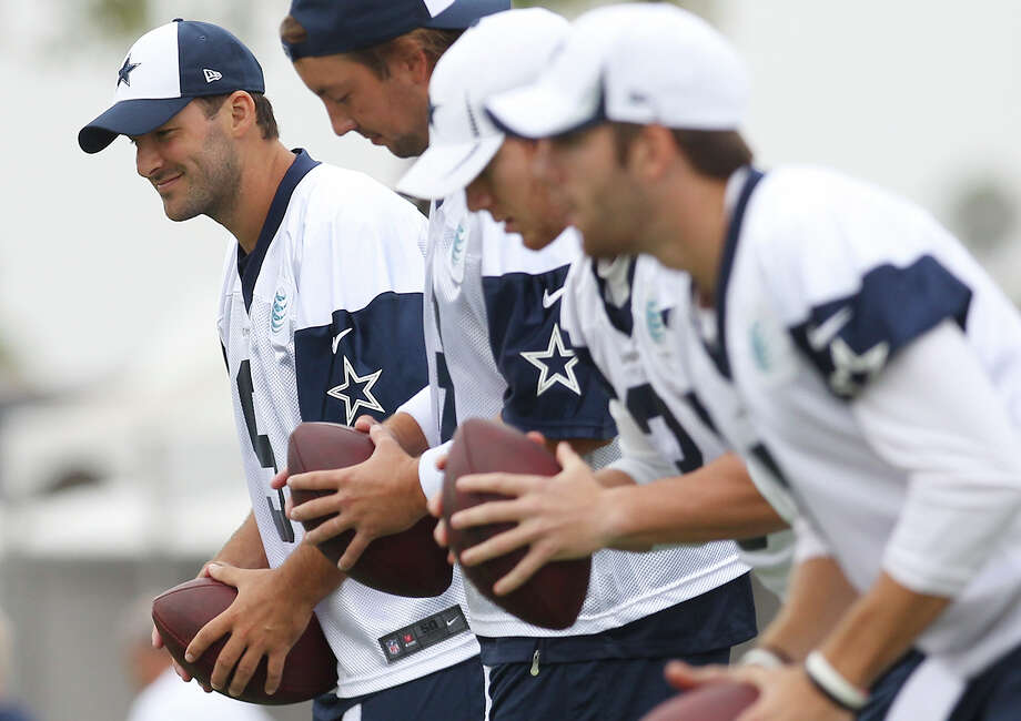 Quarterback Tony Romo (left) goes through drills at the Dallas Cowboys training camp on Sunday, July 21, 2013 in Oxnard. Photo: Kin Man Hui, San Antonio Express-News / ©2013 San Antonio Express-News