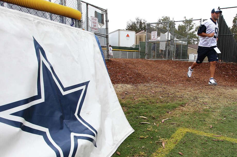 Quarterback Tony Romo heads out to the field at the Dallas Cowboys training camp on Sunday, July 21, 2013 in Oxnard. Photo: Kin Man Hui, San Antonio Express-News / ©2013 San Antonio Express-News