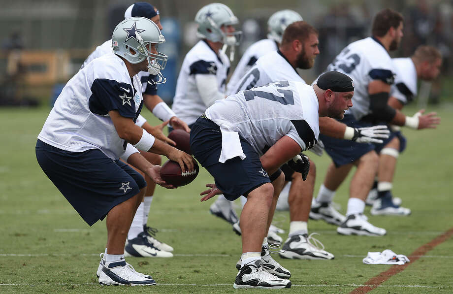Center Phil Costa (right) snaps the ball to quarterback Tony Romo at the 2013 Dallas Cowboys training camp on Sunday, July 21, 2013 in Oxnard. Photo: Kin Man Hui, San Antonio Express-News / ©2013 San Antonio Express-News