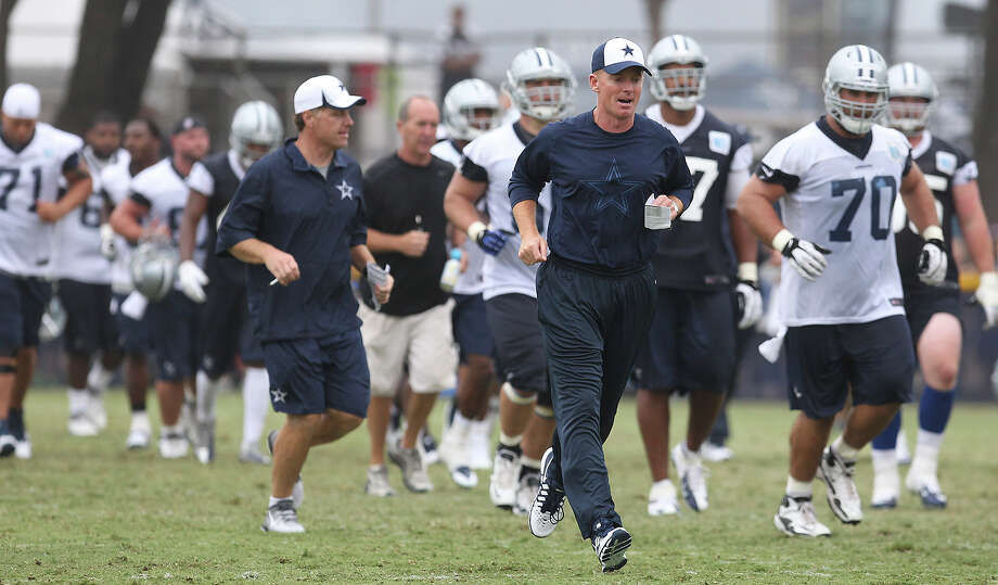 Head coach Jason Garrett runs up the field with his players at the 2013 Dallas Cowboys training camp on Sunday, July 21, 2013 in Oxnard. Photo: Kin Man Hui, San Antonio Express-News / ©2013 San Antonio Express-News
