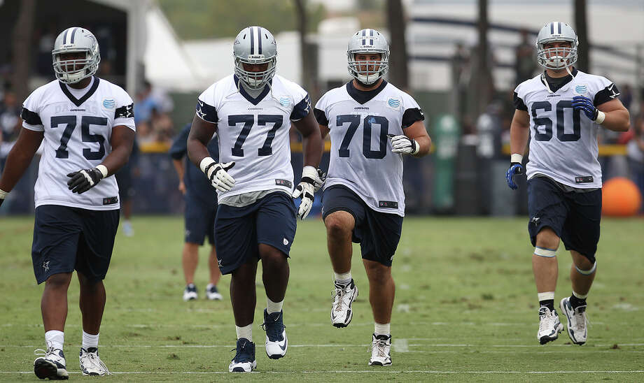Offensive lineman Darrion Weems (from left), Tyron Smith, Travis Frederick and Kevin Kowalski warm up at the 2013 Dallas Cowboys training camp on Sunday, July 21, 2013 in Oxnard. Photo: Kin Man Hui, San Antonio Express-News / ©2013 San Antonio Express-News
