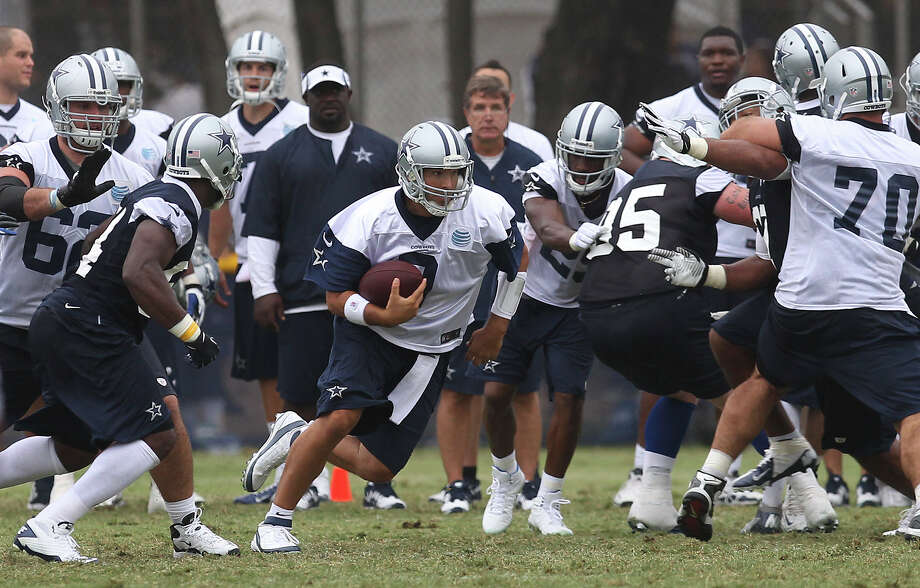 Quarterback Tony Romo runs with the ball at the 2013 Dallas Cowboys training camp on Sunday, July 21, 2013 in Oxnard. Photo: Kin Man Hui, San Antonio Express-News / ©2013 San Antonio Express-News