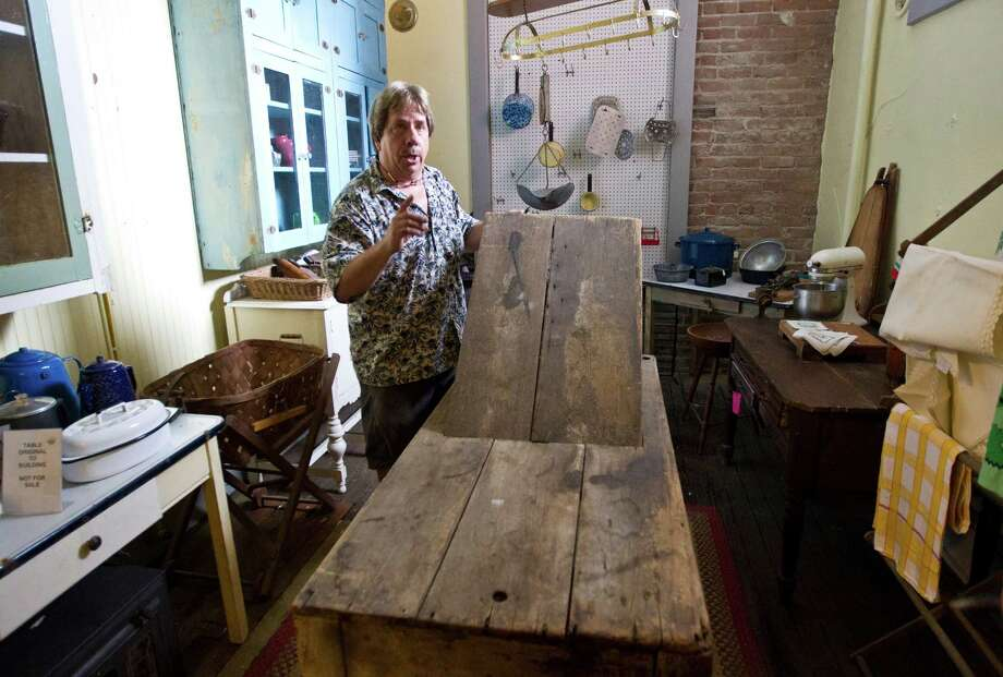 Scott Hanson, owner of the Antique Warehouse, shows a birthing table that was used when the building was the Oleander Hotel in Galveston's red-light district. Photo: Nick De La Torre, Staff / © 2013  Houston Chronicle