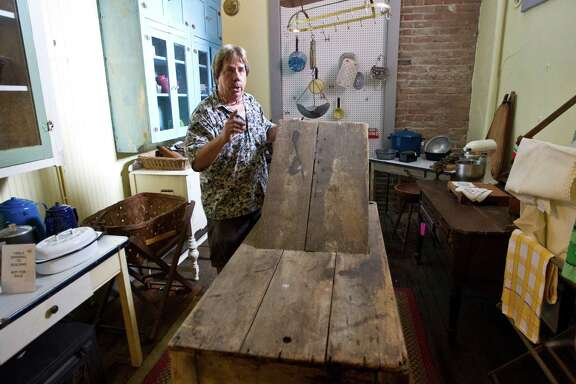 Scott Hanson, owner of the Antique Warehouse, shows a birthing table that was used when the building was the Oleander Hotel in Galveston's red-light district.