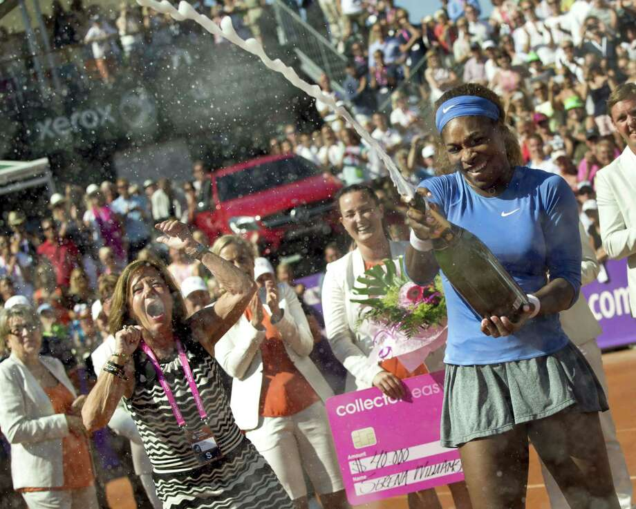 Serena Williams, right, uncorks the bubbly after beating Johanna Larsson in Sunday's Swedish Open final. Photo: BJORN LARSSON ROSVALL, Staff / AFP