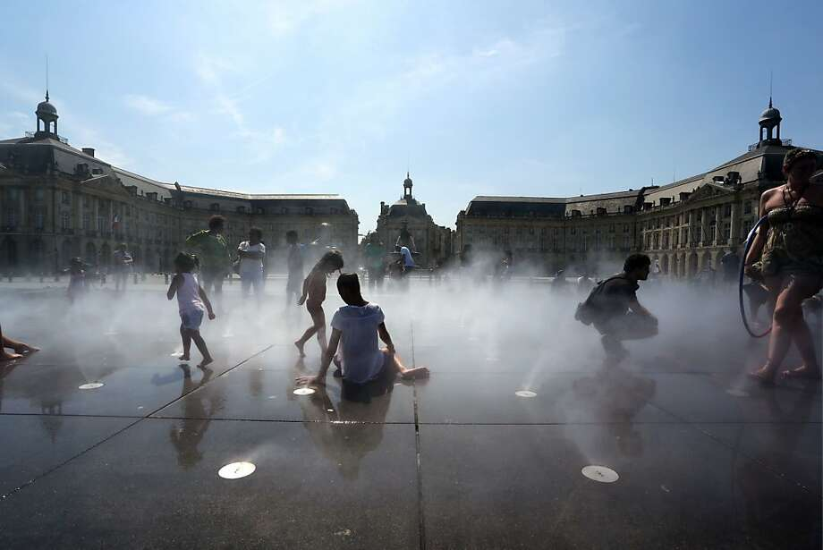 TOPSHOTS People cool off on water sprays on July 21, 2013, in Bordeaux, southwestern France. AFP PHOTO/ NICOLAS TUCATNICOLAS TUCAT/AFP/Getty Images Photo: Nicolas Tucat, AFP/Getty Images