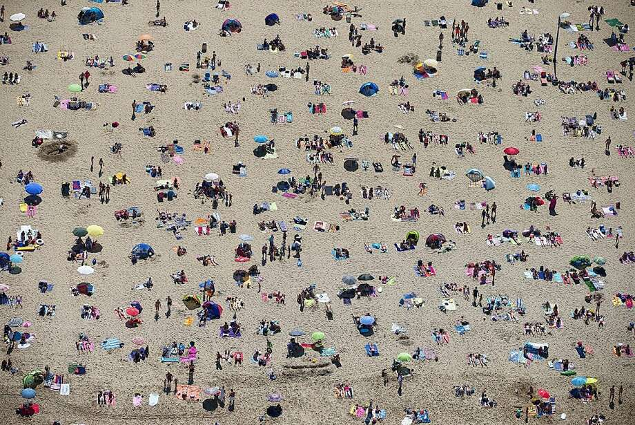 TOPSHOTS An aerial view taken on July 21, 2013 shows sunbathers crowding on the beach in Scheveningen during a warm summer day. AFP PHOTO / ANP PHOTO / JERRY LAMPEN netherlands out -JERRY LAMPEN/AFP/Getty Images Photo: Jerry Lampen, AFP/Getty Images
