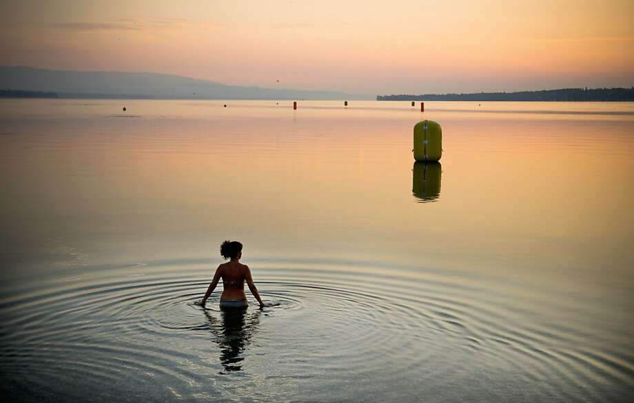 A woman takes a dip at sunrise in Lake Geneva, Geneva, Switzerland, Sunday, July 21, 2013. Temperatures are predicted to soar in Switzerland over the weekend to 34 degrees Celsius (93,2 Fahrenheit). (AP Photo/Anja Niedringhaus) Photo: Anja Niedringhaus, Associated Press