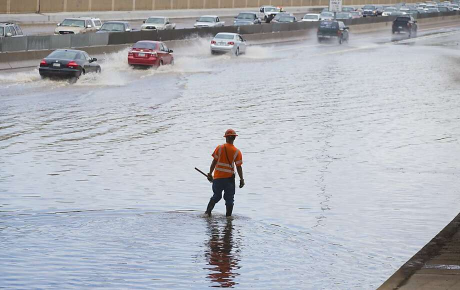 An ADOT worker unplugs a drain on the U.S. 60 after heavy rains blocked all but one lane under the Kyrene overpass in Tempe, Ariz., Sunday, July 21, 2013. (AP Photo/The Arizona Republic, Michael Chow) Photo: Michael Chow, Associated Press