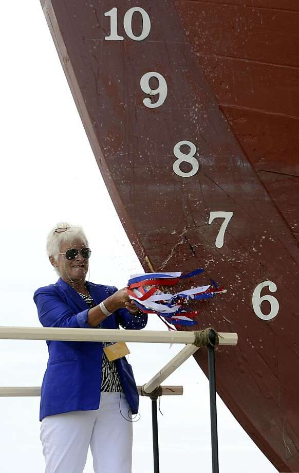Sarah Bullard, great great great granddaughter of Charles W. Morgan christens the ship bearing her ancestor's name as the Mystic Seaport launches the historic whaleship into the waters of the Mystic River, Sunday, July 21, 2013 at the seaport's H.B. duPont Preservation Shipyard in Stonington, Conn. The launch takes place on the 172nd anniversary of the ship's original launch in 1841 in New Bedford, Massachusetts. The Morgan, the last remaining wooden whaling ship remaining and the oldest American commercial vessel still in existence as well as a National Historic Landmark, is slated to embark on its 38th voyage, a tour of historic New England ports, in the spring and summer of 2014.  (AP Photo/The Day, Sean D. Elliot) Photo: Sean D. Elliot, Associated Press