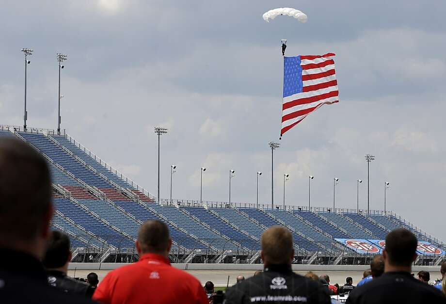A parachutist descends with a United States flag during the national anthem before the NASCAR Nationwide Series STP 300 auto race at Chicagoland Speedway in Joliet, Ill., Sunday, July 21, 2013. (AP Photo/Nam Y. Huh) Photo: Nam Y. Huh, Associated Press