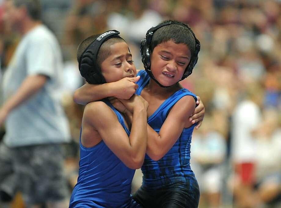 William Delgado, left, 8, of Bethlehem, Pa., is controlled by Jayden Torres, right, 7, of Lower Saucon Township, Pa., during a wrestling tournament Sunday afternoon at Louis E. Dieruff High School as part of the SportsFest 4th Annual Health & Fitness Expo iin Allentown, Pa., Sunday, July 21, 2013. (AP Photo/The Express-Times, Matt Smith) Photo: Matt Smith, Associated Press