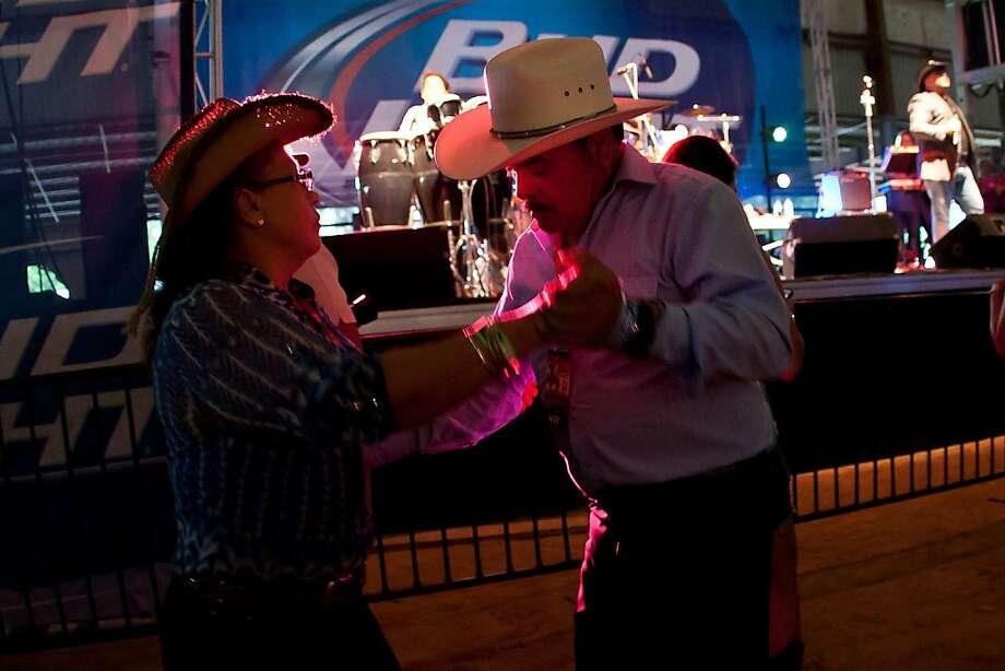 Briseida & Juan Herrera of Houston enjoy a dance during the David Olivarez set at the Tejano Music Festival, held at the Humble Civic Center Arena on Saturday, July 20, 2013, in Humble, Texas. (AP Photo/The Courier, Amanda Cain) Photo: Amanda Cain, Associated Press