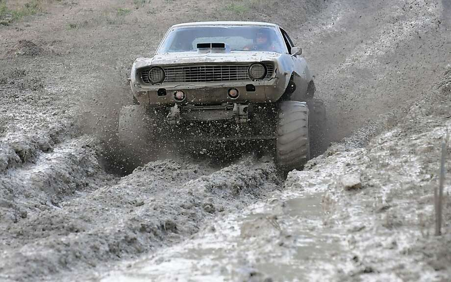 Amy Fitch drives through the mud bog in 6.02 seconds at the Boyd County Fair in Cannonsburg, Ky. Saturday July 20, 2013. (AP Photo/The Independent, Kevin Goldy) Photo: Kevin Goldy, Associated Press