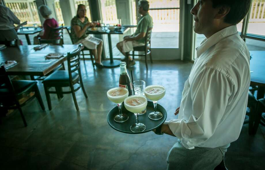 A server brings Pisco Sour's and a Coke to a table at Puerto 27 in Pacifica.