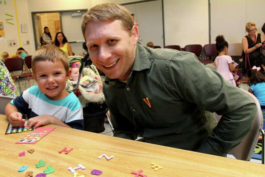 Parker Noyes, 4, of Katy enjoys making a bookmark with Bryan Kratish, the new children's librarian at Katy Branch Library.  Parker Noyes, 4, of Katy enjoys making a bookmark with Bryan Kratish, the new children's librarian at Katy Branch Library. Photo: Suzanne Rehak, Freelance Photographer