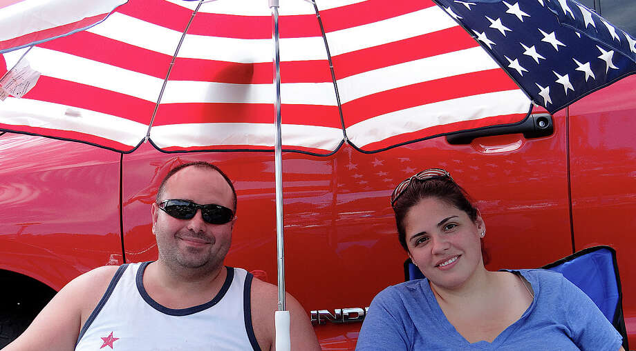 Vendor Gabe and Rosa Ferreira stay cool under an umbrella at their display table Sunday sponsored by Fairfield Warde High School PTA's flea market. Photo: Mike Lauterborn / Fairfield Citizen contributed