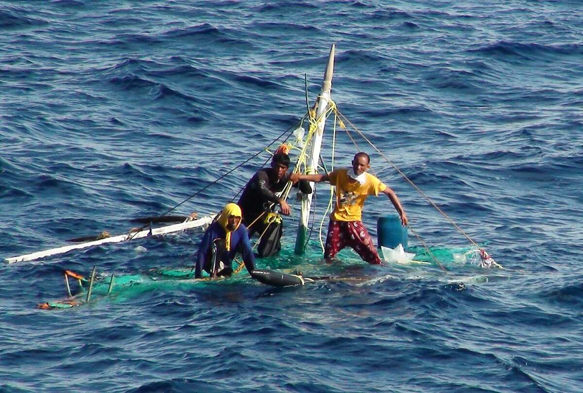 Three men in a tub: Filipino fishermen hang on to what remains of their boat as they wait to be rescued off Kaohsiung, Taiwan. The trio spent five days adrift after a storm blew their small craft hundreds of miles off course.