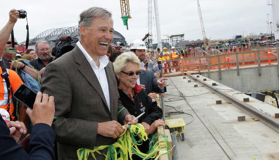"Washington Gov. Jay Inslee, left, and former Gov. Chris Gregoire, right, react to applause, Saturday in Seattle, after they took part in the christening of ""Bertha,"" a massive tunnel-boring machine that is expected to spend the next 14 months boring a two-mile tunnel to replace the 60-year-old Alaskan Way Viaduct, a double deck highway along the downtown Seattle waterfront. Photo: Ted S. Warren, AP / AP"