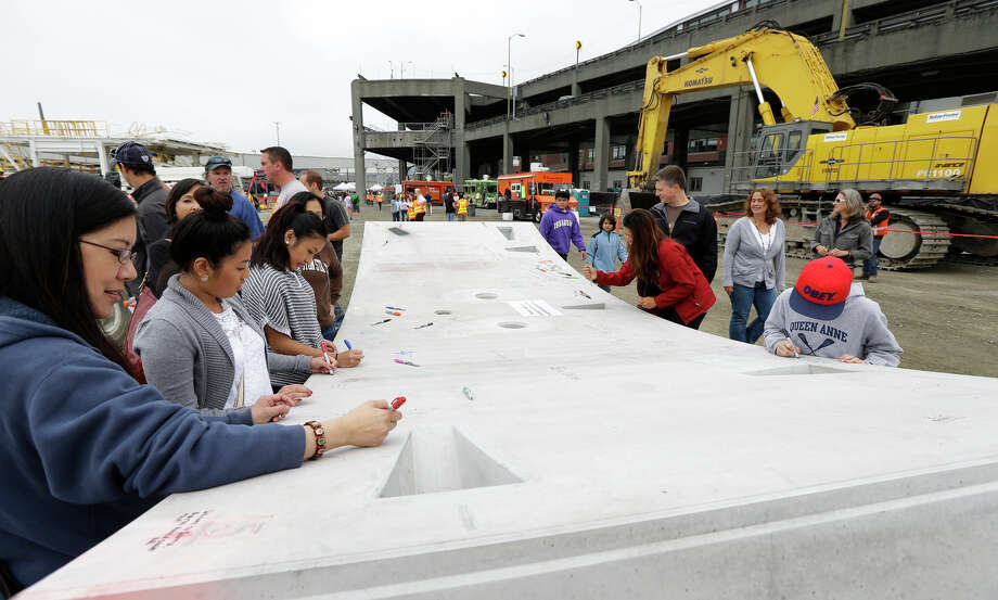 Members of the public write messages Saturda, on a section of curved concrete that will make up the walls of a tunnel being drilled along the downtown Seattle waterfront to replace the aging elevated Alaskan Way viaduct highway shown in the background. The Washington Department of Transportation held an open house Saturday for the public to view progress on the tunnel project. Photo: Ted S. Warren, AP / AP