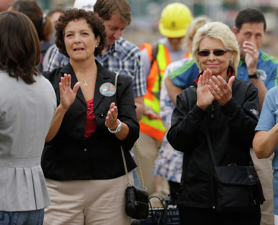 "Former Washington Gov. Chris Gregoire, right, and former Transportation Secretary Paula Hammond, left, applaud during a ceremony to christen ""Bertha,"" the massive tunnel-boring machine that is expected to spend the next 14 months drilling a two-mile tunnel to replace the 60-year-old Alaskan Way Viaduct, Saturday in Seattle. The tunnel will replace the viaduct, a double deck highway along the downtown Seattle waterfront. Photo: Ted S. Warren, AP / AP"