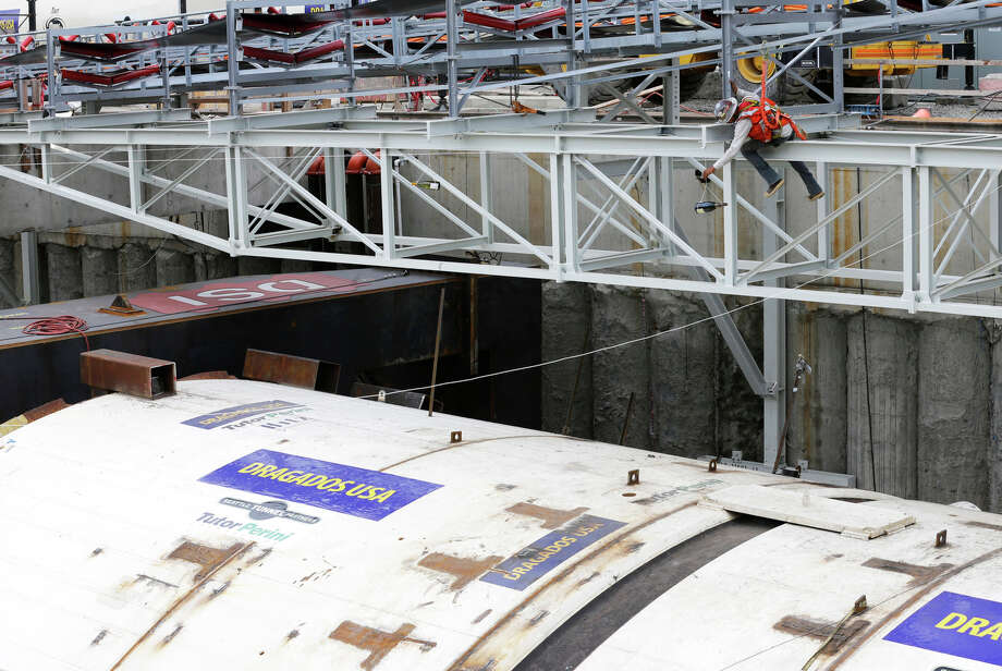"A worker positions a bottle of Spanish Cava on a rope above ""Bertha,"" the massive tunnel-boring machine that is expected to spend the next 14 months drilling a two-mile tunnel to replace the 60-year-old Alaskan Way Viaduct, prior to a christening ceremony, Saturday in Seattle. The machine is so massive that instead of striking it with bottles, officials cut three ropes to release bottles of wine, Japanese sake, and Spanish Cava to christen the machine. Photo: Ted S. Warren, AP / AP"