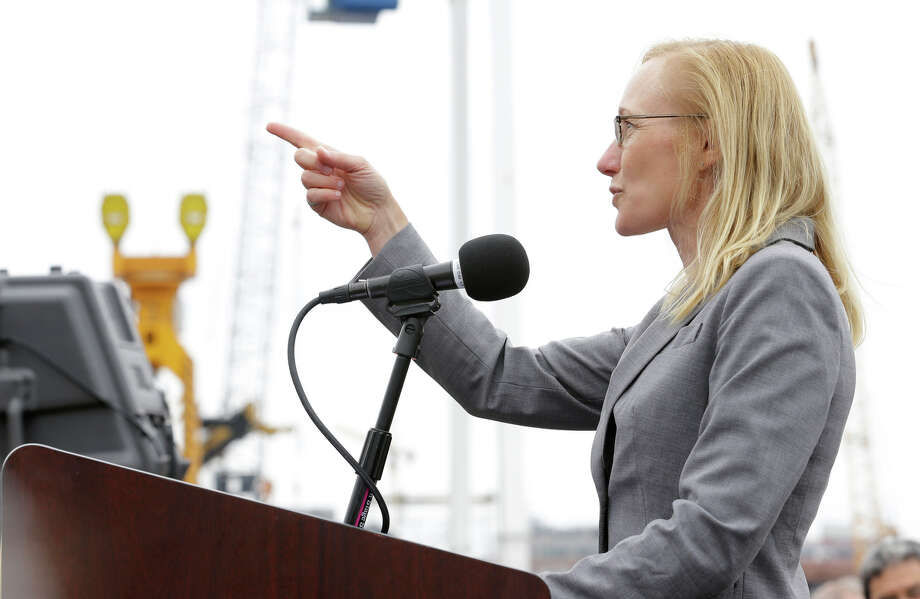 Washington Secretary of Transportation Lynne Peterson points to the Alaskan Way Viaduct elevated roadway that will be replaced by a two-mile waterfront tunnel, Saturday as she speaks at a christening ceremony for the tunnel-boring machine in Seattle. Photo: Ted S. Warren, AP / AP