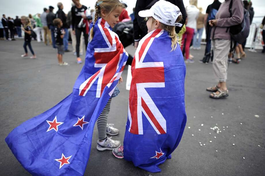 Georgia Dagg (L), whose father James Dagg is a trimmer on the Team New Zealand boat ,and Ellie Holroyd, whose father is a designer for Team New Zealand, wrapped themselves in New Zealand flags as they wait for the start of the The Louis Vuitton Cup race.