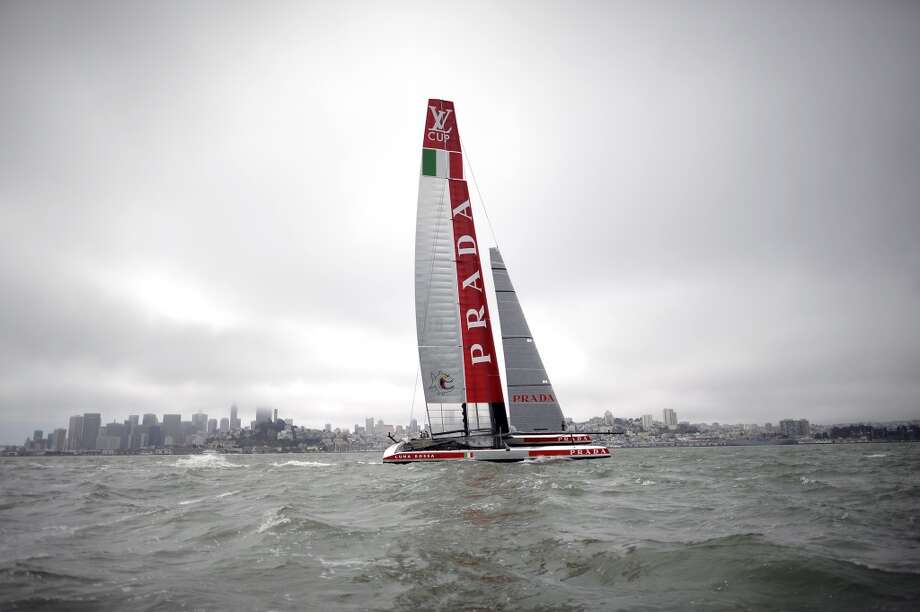 Team Luna Rossa Challenge passes by before the start of The Louis Vuitton Cup Race against Team Emirates.