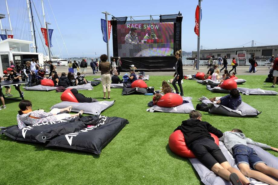 Fans lay on bean bags as they watch commentary following the Louis Vuitton Cup race at the America's Cup Pavilion.