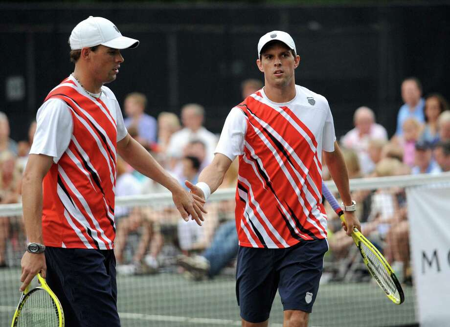 Bob Bryan, left, and his twin brother, Mike, right, high-five during a professional tennis exhibition at the Lake Club in Wilton, Conn., on Saturday, August 25, 2012. Photo: Lindsay Niegelberg / Stamford Advocate
