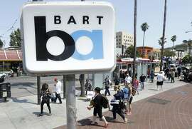 Riders walk from a Muni bus near the 24th Street Mission Bay Area Rapid Transit (BART) station in San Francisco, Monday, July 1, 2013. Early Monday, July 1, 2013, two of San Francisco Bay Area Rapid Transit's largest unions went on strike after weekend talks with management failed to produce a new contract. (AP Photo/Jeff Chiu)