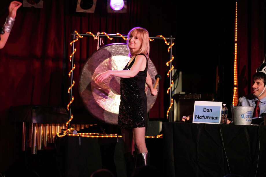 "Radio and television personality Leslie Gold makes for the gong during one of the recent performances of ""The Gong Show Live."" Gold, who lives in Fairfield, is the executive producer for the off-Broadway show, which is a theatrical representation of the 1970s television show hosted by Chuck Barris. A rotating cast has been presenting monthly shows at The Cutting Room in Manhattan since December 2012. The remaining performances are Sept. 12 and Oct. 3, 2013. Photography by Marc Birnbach Photo: Contributed Photo"