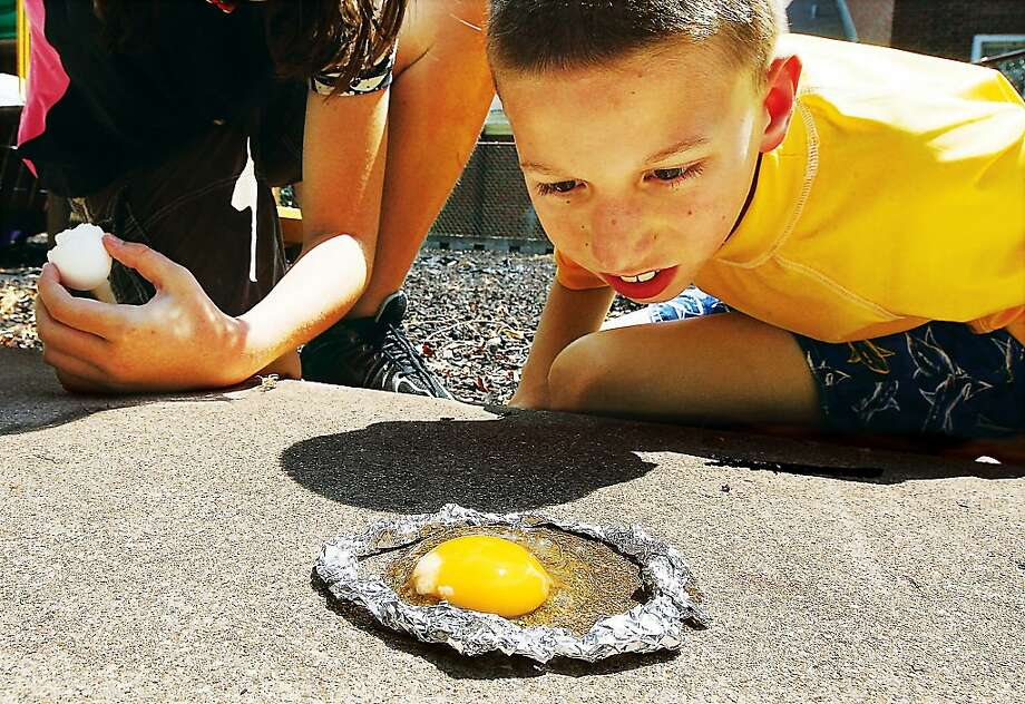 Nation still gripped by a widespread desire cook eggs on rocks: In Alton, Ill., 10-year-old William Roderfeld watches an egg do nothing at YWCA Child Enrichment Summer 