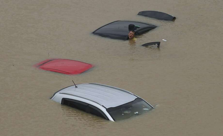 Hardly worth the effort:A man struggles to move a submerged car after a torrential rain caused major flooding in 