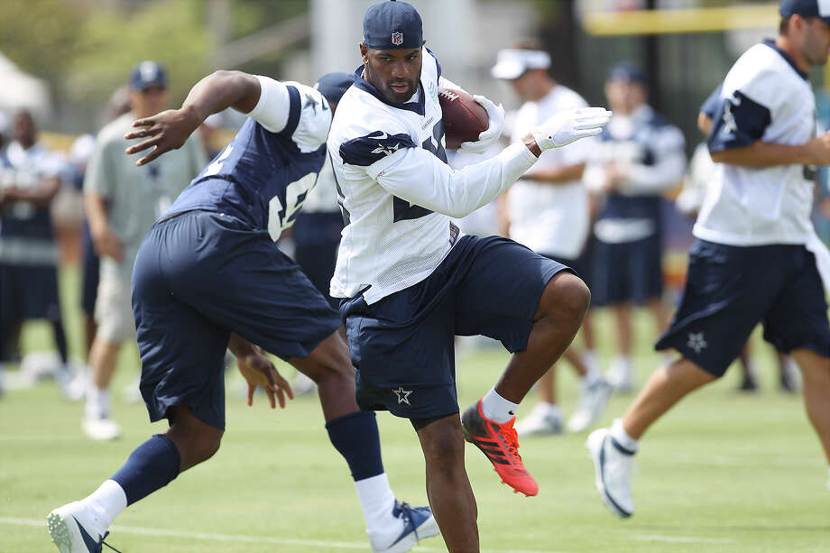 Running back DeMarco Murray (29) runs around DeMarcus Ware (94) during morning practice at the 2013 Dallas Cowboys training camp on Monday, July 22, 2013 in Oxnard. Photo: Kin Man Hui, San Antonio Express-News / ©2013 San Antonio Express-News