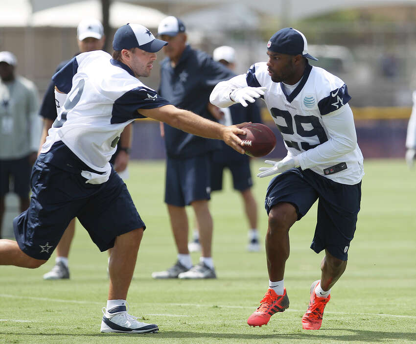 Quarterback Tony Romo (left) hands off the ball to running back DeMarco Murray (29) during morning practice at the 2013 Dallas Cowboys training camp on Monday, July 22, 2013 in Oxnard.