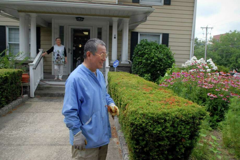 Retired surgeon Chan-Kook Rha and his wife Lori at their Bedford St home in Stamford, Conn. on Monday July 22, 2013. He tends the garden and they both have taken up photography traveling around the US and also attending workshops. Photo: Dru Nadler / Stamford Advocate Freelance
