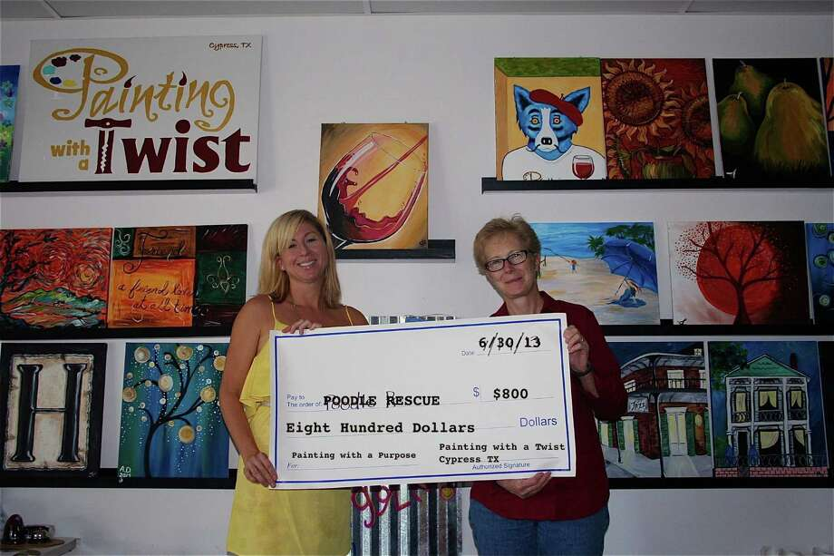 Painting with a Twist owner, Andrea O'Dowd (left) donated an $800 check to Poodle Rescue of Houston volunteer Kate Howard. Photo: Courtesy Of Painting With A Twist